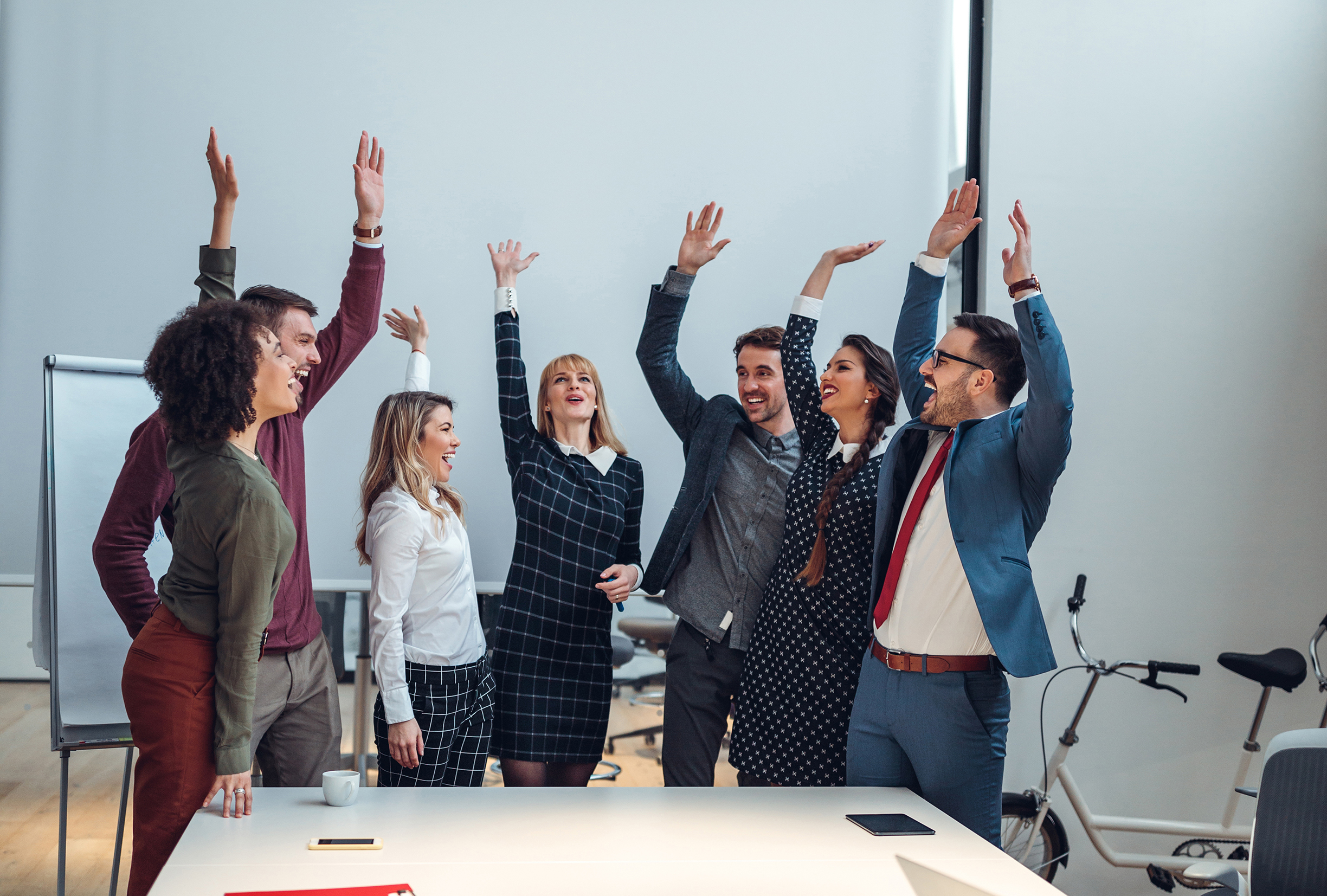 Vertical shot of a group of coworkers cheering in an office