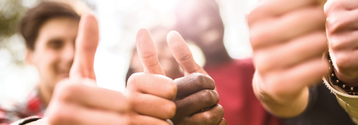 college student multiracial thumbs up at dusk