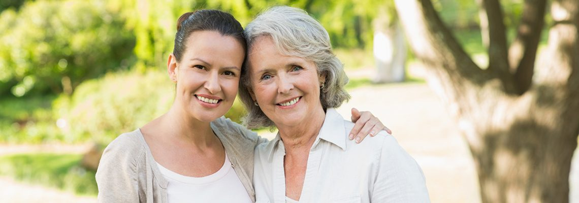 Portrait of a smiling mature woman with adult daughter at the park